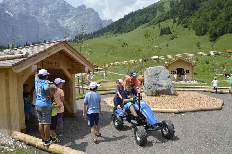Alle Kinder möchten auf dem Abenteuerspielplatz in Tirol mit diesen Tretautos fahren