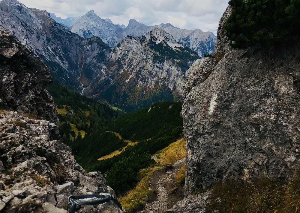 Durch die Felsen geht der Wanderweg, hinten ist das Karwendel schön zu sehen