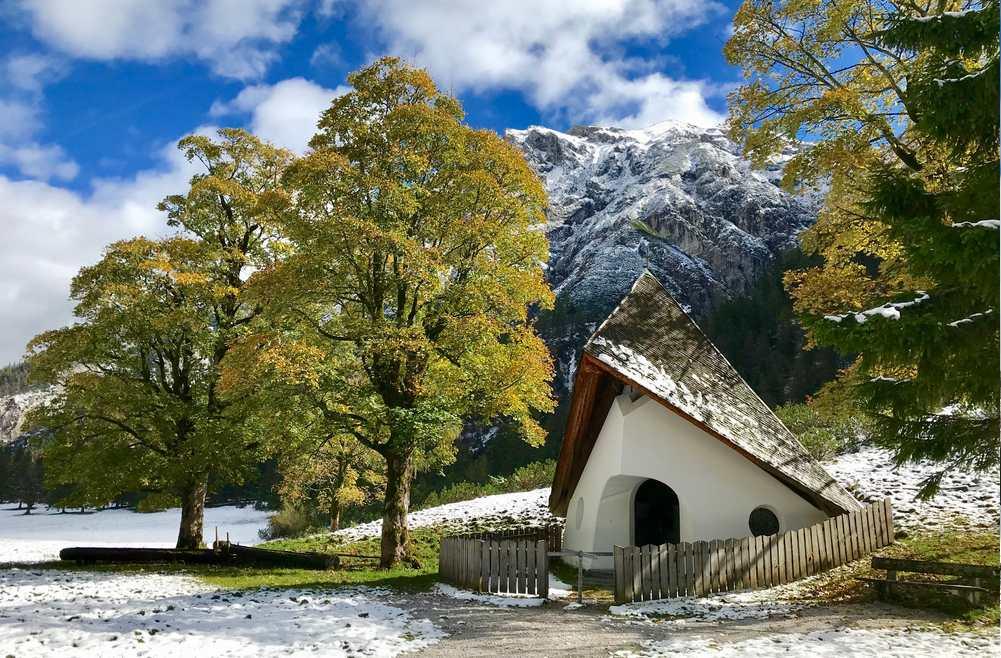In den Bergen liegt der Schnee, die Bäume leuchten goldgelb im Karwendel