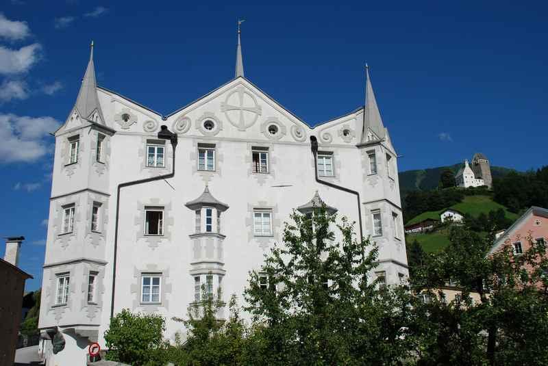 Das Fuggerhaus ins Schwaz hat eine besondere Form, die Erker ragen exzentrisch in den Himmel, hinten ist die Burg Freundsberg zu sehen
