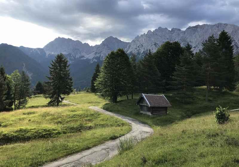 Oberhalb der Gröblalm verläuft dieser schöne Kranzberg Wanderweg mit Blick auf das Karwendel. Typisch für die Gegend sind die Heuhütten aus Holz.