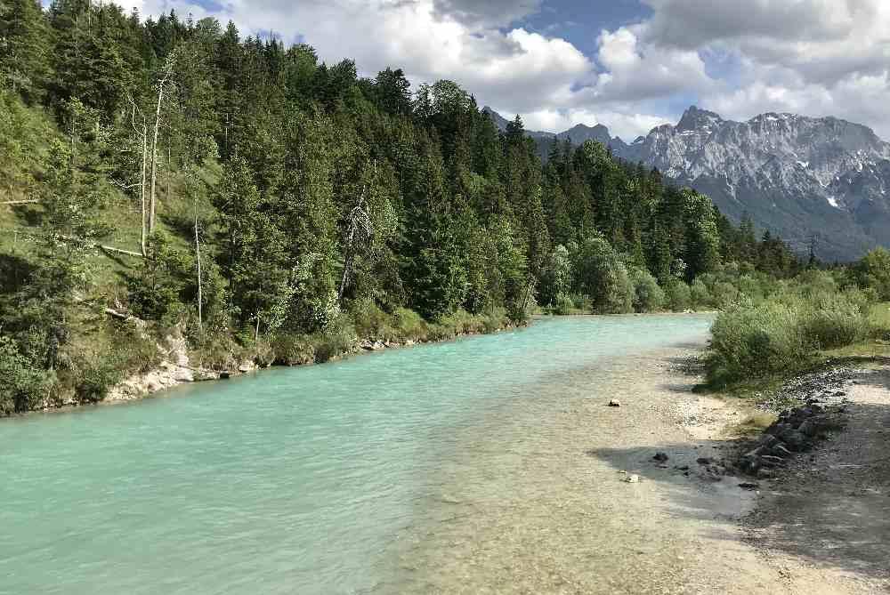 Diesen Blick auf die türkisgrüne Isar mit dem Karwendel hast du auf dem Isar Natur Erlebnisweg