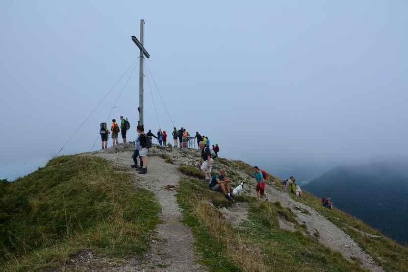 Selbst bei schlechtem Wetter triffst du auf der Jochberg Wanderung Leute am Gipfel