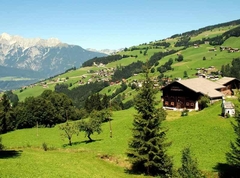 Der idyllische Ort Kolsassberg in den Tuxer Alpen, unten das Inntal, am Horizont das wunderschöne Karwendelgebirge