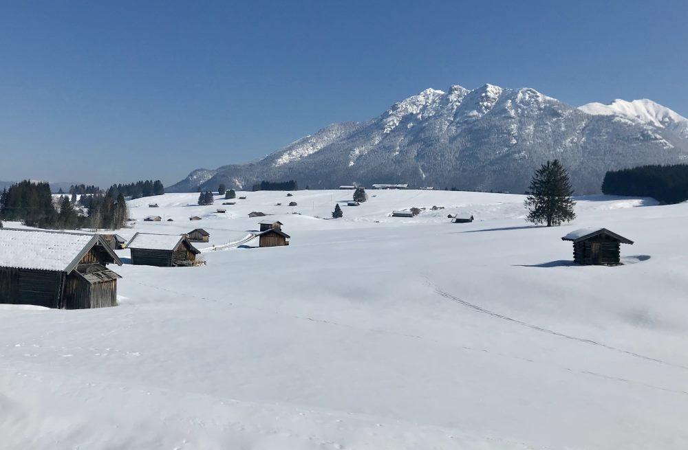Über die verschneiten Buckelwiesen wandern, vorbei an den Holzstadeln samt Karwendelblick