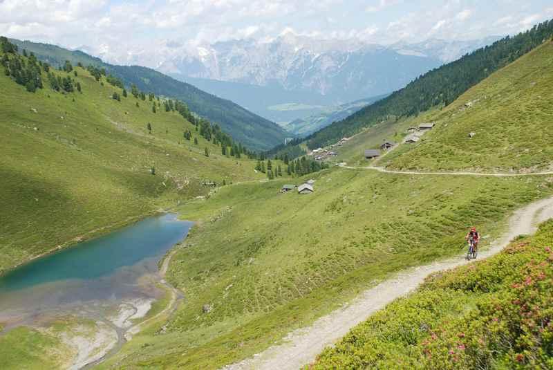Der Nafingsee von oben gesehen: Mit der Weidener Hütte, der Nafingalm und dem Karwendel; ein Mountainbiker fährt auf der Transalp Etappe