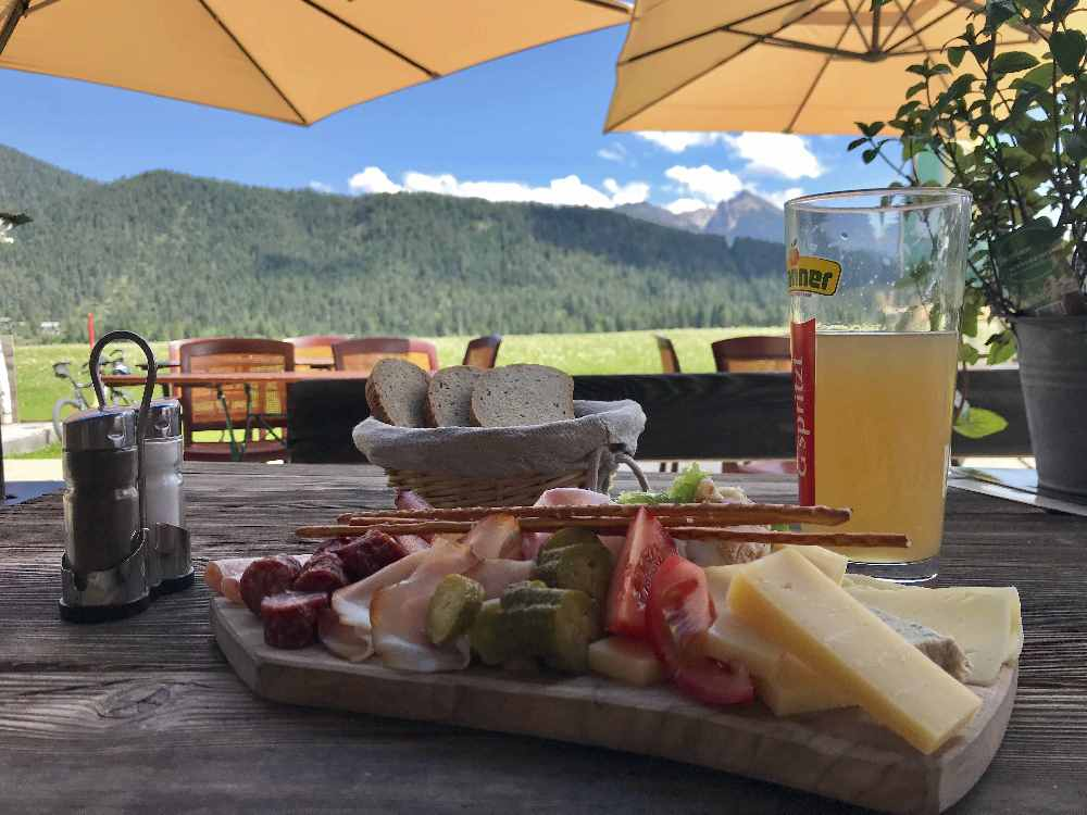 Brotzeit im Tal mit Bergblick auf der Sonnenterrasse bei Poli´s Hütte