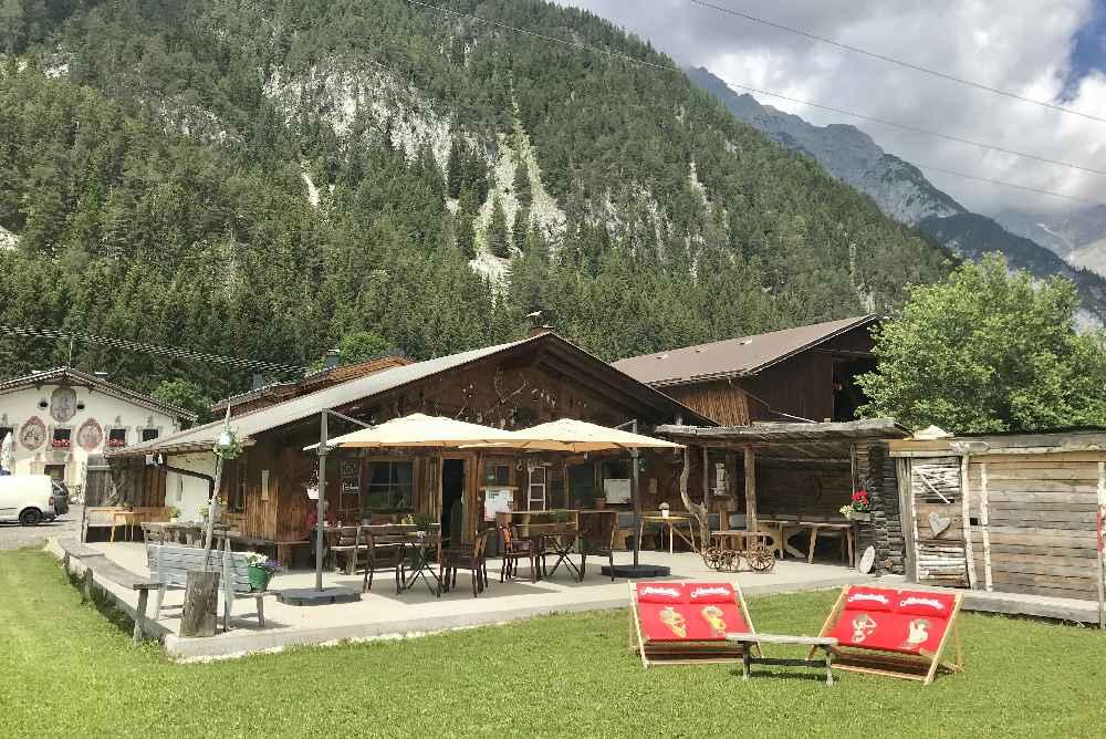 So urig ist die Hütte von vorne gesehen, mit den großen Liegestühlen zum Sonnen