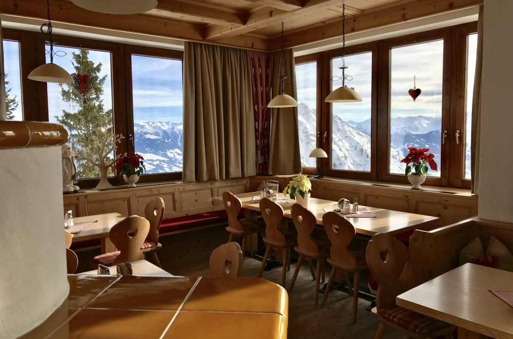 Neben dem warmen Kamin stehen die gemütlichen Tische mit Blick auf die Berge