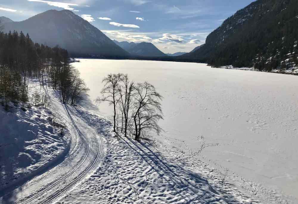Am zugefrorenen Sylvensteinsee führt links die Langlaufloipe von Fall nach Vorderriß