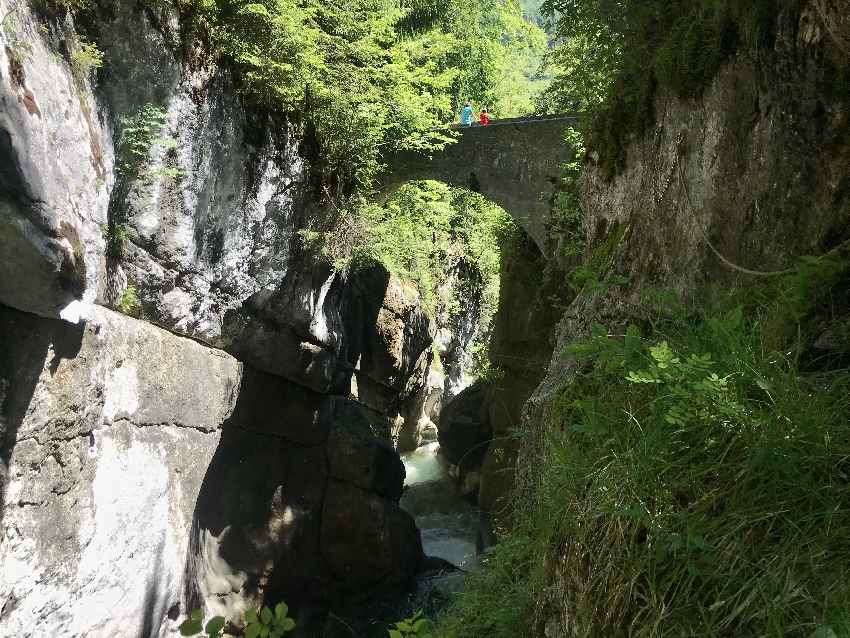 Der Obere Tatzelwurm Wasserfall mit der Steinbrücke - schau die Dimension zwischen den Menschen auf der Brücke und der Tatzelwurm Schlucht!