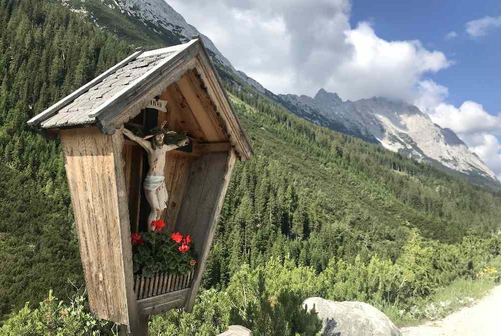 Bei diesem Bildstock siehst du hinter dir das Karwendel, links das Mieminger Gebirge und rechts das Wettersteingebirge