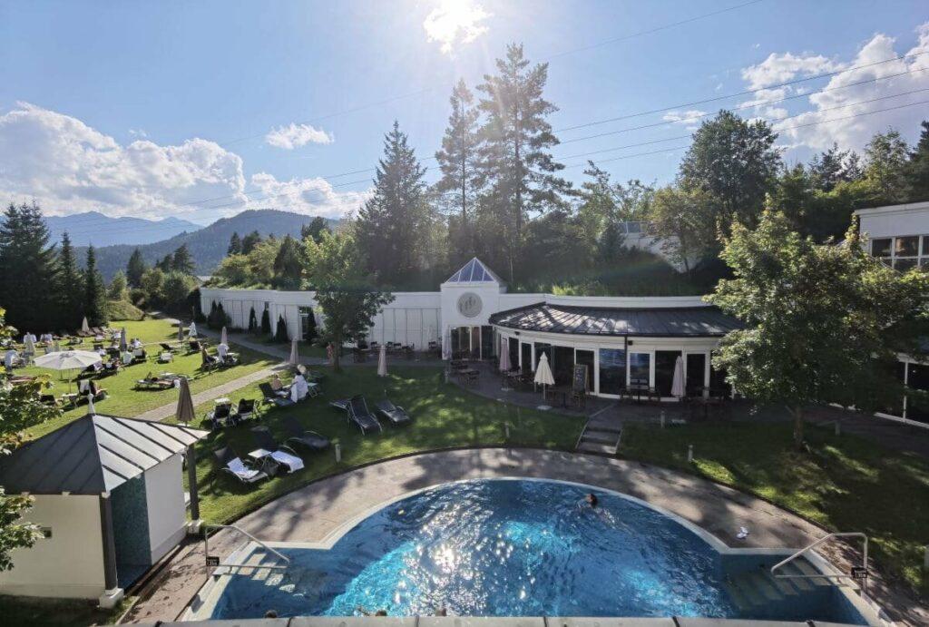 Der Blick vom Krumers Alpin Resort auf den Pool im Garten und die große Liegewiese