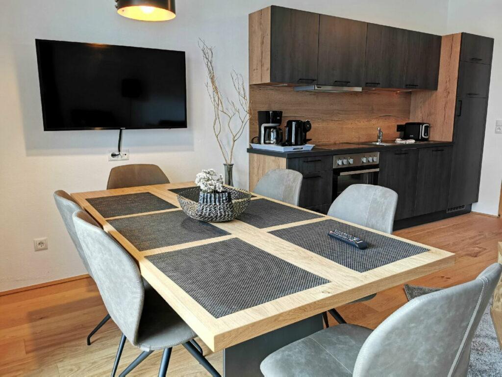 Das Wohnzimmer der Ferienwohnung mit Esstisch und Küchenzeile